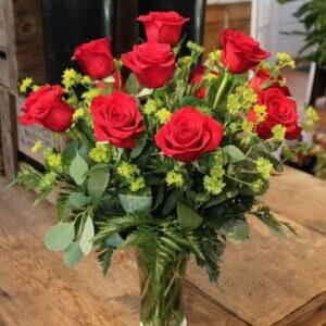 one dozen roses arranged with premium greens in glass vase