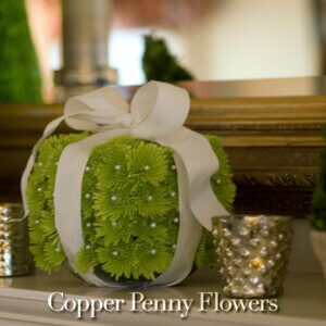 christmas present decorated with green mums, pearls, and a bow