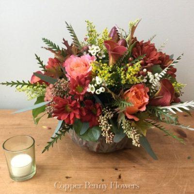 Artisanal Autumn flower arrangement features rust and orange roses in a keepsake bowl