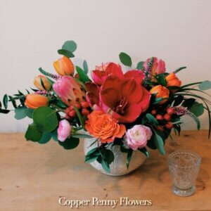 Dress Up flower arrangement featuring rouge amaryllis, orange tulips, and pink ranunculus