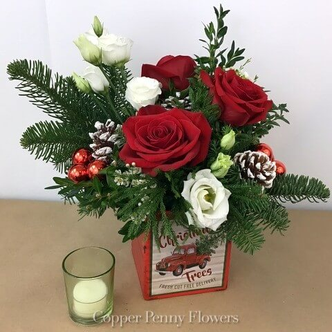 Merry Vintage features a holiday flower arrangement in reds and whites with evergreens in a vintage box