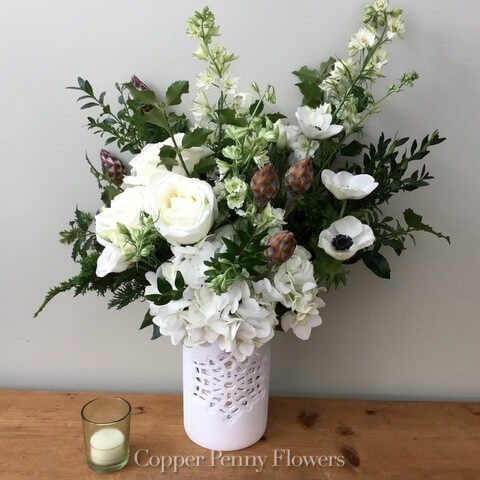 Snow Happy is a winter arrangement with greens and white flowers and cones in a snowflake vase