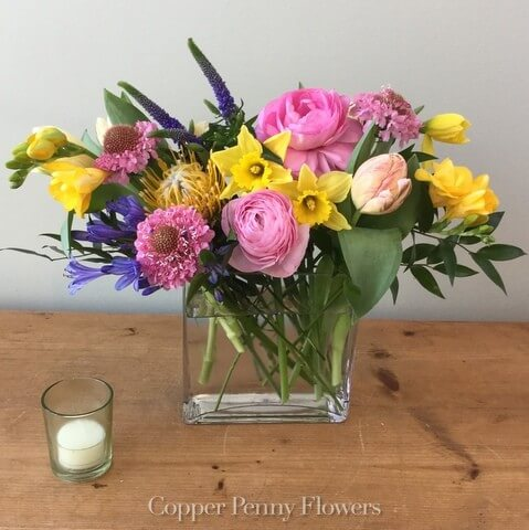 Spring for Joy flower arrangement is a bright mix with yellow daffodils and pink ranunculus in a glass rectangle