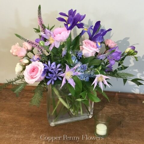 Singing Spring is a cheerful pink and purple arrangement in a glass cube