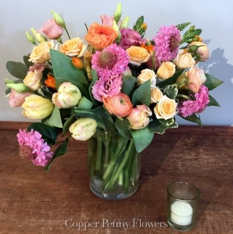 Pleased As Punch is festive flower arrangement featuring coral, pink, and yellow blooms