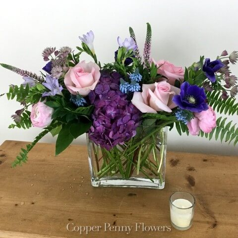 Kindest Heart flower arrangement featurs purple, blue and pink flowers in a glass rectangle