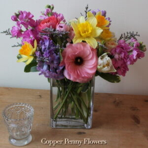 Come Spring flower arrangement featuring stock, daffodils, and ranunuculus in pinks and yellows and purples