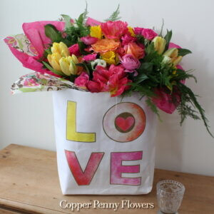 Love Blooms Bouquet is bright spring bouquet in reusable paper bag