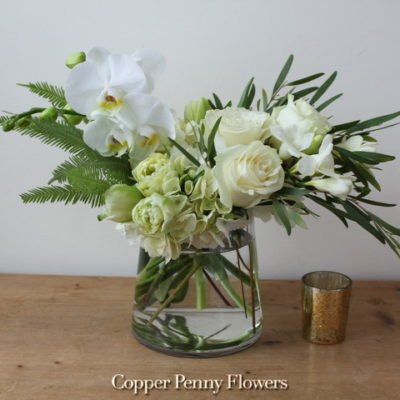 Paradise white floral arrangement with orchids, roses, and premiun greens