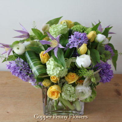 Garden Dreaming arrangement in purple, yellow, green, and white featuring hyacinth, roses, and viburnum
