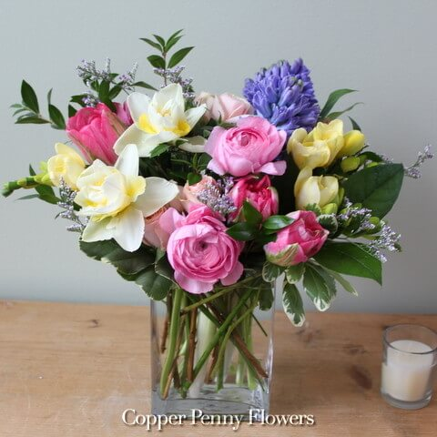 Come Spring flower arrangement with daffodils, ranunculus, and hyacinth
