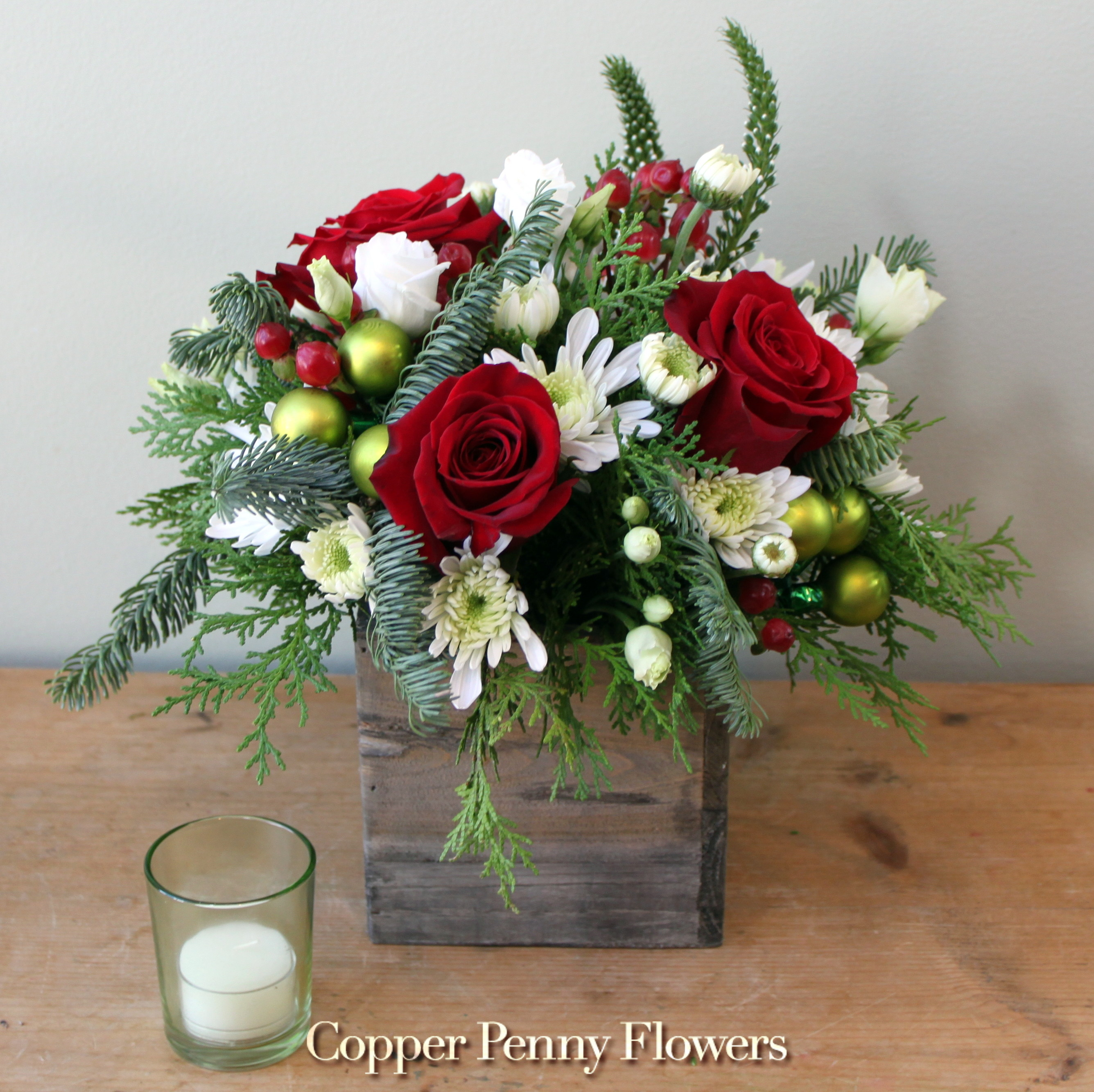 Evergreen Hello features red roses with evergreens and white flower accents in a wooden box