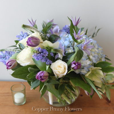 Blue Moon flower arrangement features blue hydrangea with white roses and purple tulips in a glass bowl