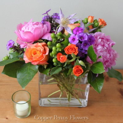 Color Me Joy features orange, hot pink, and purple blooms in a glass rectangle vase
