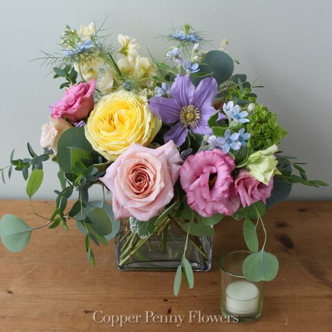 Sweet arrangement of pastel blooms in a glass cube