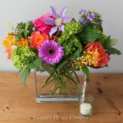 Color Me Joy bright mixed flower arrangement in a glass rectangle