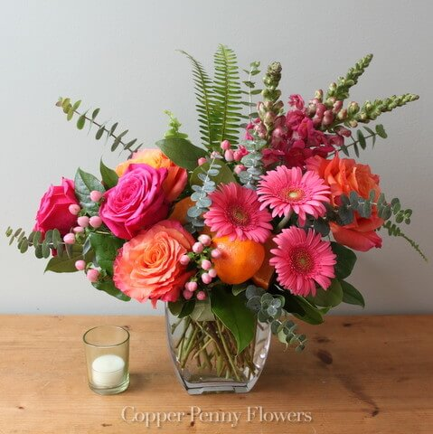 Citrus Fiesta flower arrangement features hot pink and orange blooms with premium greens