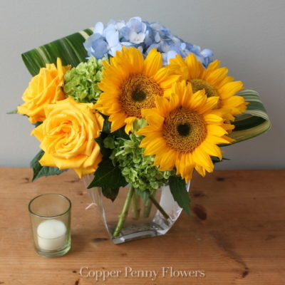 Sun and Sky flower arrangement features yellow sunflowers and roses with blue and green hydrangea