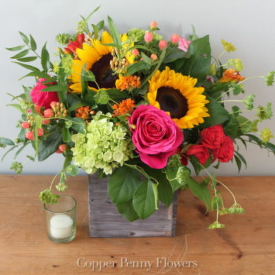 Jubilee flower arrangement features sundlowers, roses, and hydrangea in a wooden box