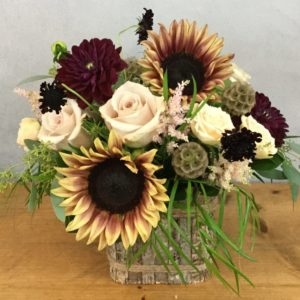 Villa Vintage flower arrangement features creamy roses with bi-color sunflowers and garden accents in a birch cube