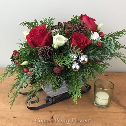 Jingle All The Way arrangement features evergreens and red roses and pine cones in a sleigh