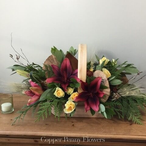Woodland Mambo flower arrangement is greenery and roses and lilies in a wooden basket