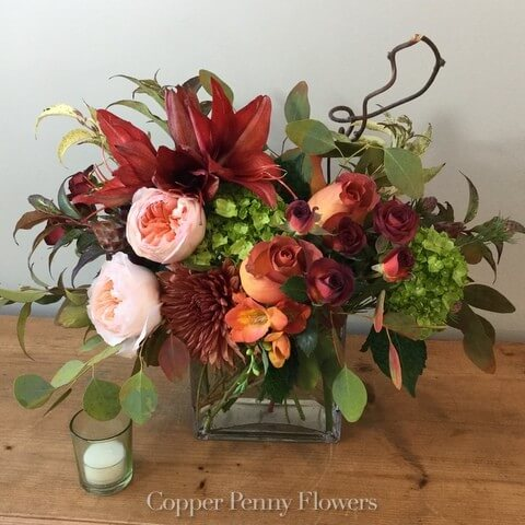 Pumpkin Spice flower arrangement features roses, garden roses, hydrangea and lilies or amaryllis with unique foliage and accents in a glass cube.