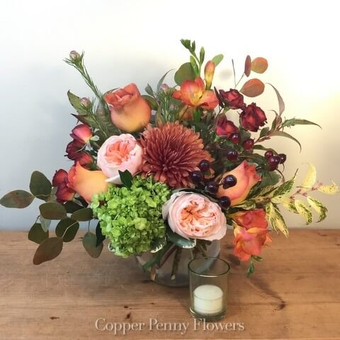 Sunset flower arrangement features peach and rust blooms with green hydrangea