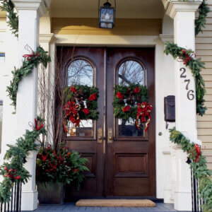double front doors with festive everygreen wreaths and garland decorationss