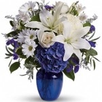 Beautiful blooms such as blue hydrangea, crème roses, white lilies, and alstroemeria along with yellow and white chrysanthemums, eucalyptus, limonium and more are beautifully arranged in a dazzling cobalt blue vase.