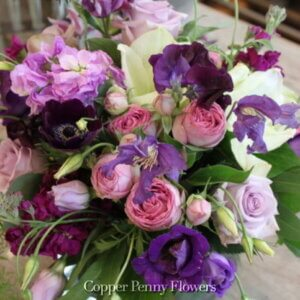 hand-held bouquet of purples, pinks, and whites