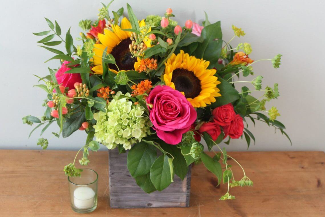 Jubilee flower arrangement features sunflowers, green hydrangea, and hot pink roses in a rustic wooden container