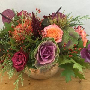 Plumberry is kale, protea, and roses in a gold bowl