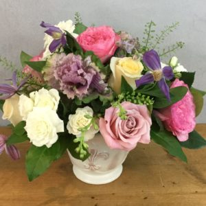 Rose Lane flower arrangement features pink, lavender, and white roses in a fleur de lis vase