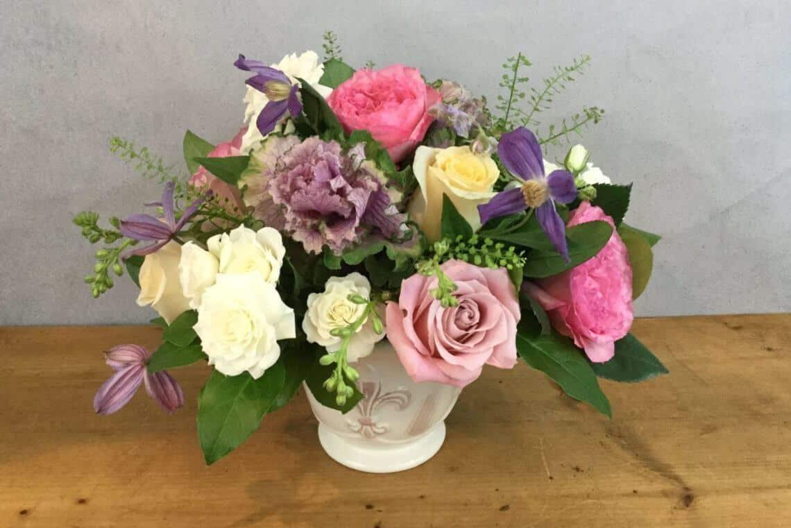 Rose Lane flower arrangement features pink, lavender, and white roses in a fleur de lis vase